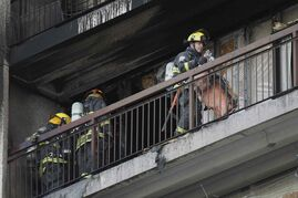 Firefighters attend a fire on an apartment balcony at 429 Westwood Drive Sunday.