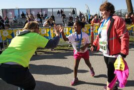 Amy McClusky, 8, gives Karen Timchuk, a cancer survivor, a high-five after crossing the finish line with her mom, Linda (right) this morning.