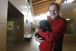 Bill McDonald, holding a puppy named Holly at the humane society, is excited about his new job.