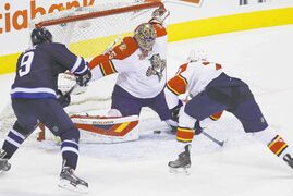 The Panthers' Tom Gilbert (77) tips the shot by Jacob Trouba (not shown) through the legs of goaltender Jacob Markstrom as Evander Kane (9) looks for a rebound.