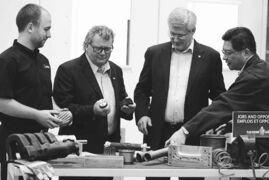 Minister of State for Science and Technology Ed Holder (second from left) and Prime Minister Stephen Harper look over devices fabricated on 3D printers at the National Research Council in London, Ont.