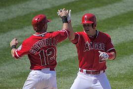 Los Angeles Angels' Mike Trout, right, is congratulated by Johnny Giavotella after hitting a two-run home run during the seventh inning of a baseball game against the Texas Rangers, Sunday, April 26, 2015, in Anaheim, Calif. The Rangers won 5-4. (AP Photo/Mark J. Terrill)