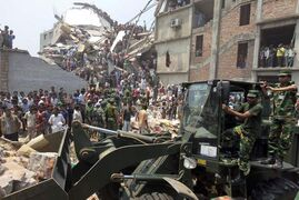 Almost one year ago, Bangladeshi soldiers use an earth mover for rescue operations after the eight-storey building housing several garment factories collapsed in Savar, near Dhaka, Bangladesh.