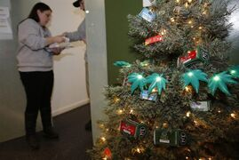 In this photograph taken on Thursday, Nov. 20, 2014, a Christmas tree decorated with lighted marijuana leaves sits in the foreground as bud tenders Maggie Slattery, back left, and John Satterfield check over customer's order in a recreational marijuana shop in northwest Denver. (AP Photo/David Zalubowski)