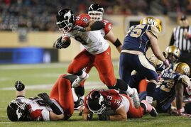 Calgary Stampeders' Jon Cornish (9) runs for yards against the Winnipeg Blue Bombers during the second half of CFL action in Winnipeg Saturday, October 18, 2014.