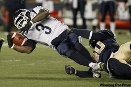 Toronto Argonauts' Cory Boyd (3) gets taken down by Winnipeg Blue Bombers' Odell Willis (40) during the first half of their CFL game in Winnipeg Friday.