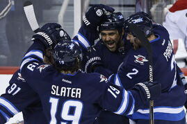 Winnipeg Jets' Jiri Tlusty (91), Jim Slater (19), Dustin Byfuglien (33) and Adam Pardy (2) celebrate Byfuglien's goal against Montreal Canadiens goaltender Dustin Tokarski (35) during first period NHL action in Winnipeg on Thursday.