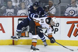 Winnipeg Jets' Andrew Ladd (16) gets the check on Anaheim Ducks' Francois Beauchemin (23) during first period NHL game 3 playoff action in Winnipeg.