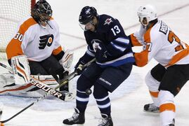 Winnipeg Jets' Kyle Wellwood, centre, fights for the puck with Philadelphia Flyers' Jay Rosehill as goaltender Ilya Bryzgalov looks for the rebound during first period NHL action in Winnipeg on Saturday. The Jets rebounded and led the Flyers 4-1 in the second period.