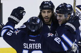 Winnipeg Jets' Jim Slater (19), Chris Thorburn (22) and Anthony Peluso (14) celebrate Thorburn's goal against the Buffalo Sabres during third period NHL action in Winnipeg on Tuesday.