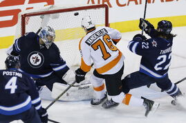 Jets goalie Ondrej Pavelec looks back as the Flyers' Chris VandeVelde rings a shot off the crossbar Sunday. Jets winger Chris Thorburn (22) charges back to defend.