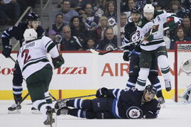 Winnipeg Jets' Mathieu Perreault (85) goes down to block the shot from Minnesota Wild's Keith Ballard (2) during second period action. The Jets won 2-1.