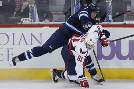 Winnipeg's Adam Pardy (2) tangles with Washington's Steve Oleksy (61) in the first period Tuesday evening.