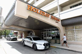 A police car sits outside the Holiday Tower Sunday.