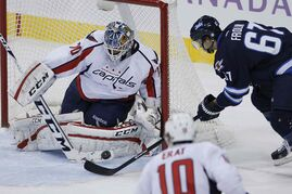 Washington Capitals goaltender Braden Holtby makes a save on a close-in scoring attempt by Winnipeg Jets forward Michael Frolik during first-period NHL action at the MTS Centre in Winnipeg Tuesday.