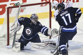 Winnipeg Jets' goaltender Al Montoya (35) stops the shot from the point as Calgary Flames' Jiri Hudler (24) and Jets' Matt Halischuk (15) look for the rebound during first period NHL action in Winnipeg on Monday, Nov. 18, 2013.