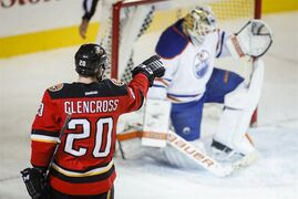 Edmonton Oilers goalie Ben Scrivens, left, picks himself up after Calgary Flames' Curtis Glencross scored during third period NHL hockey action in Calgary, Saturday, Dec. 27, 2014.THE CANADIAN PRESS/Jeff McIntosh