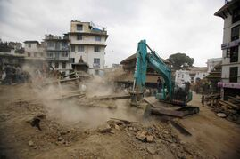 A crane removes debris from the site of a building that collapsed in an earthquake in Kathmandu, Nepal on Saturday. A magnitude 7.9 quake shook Nepal's capital and the densely populated Kathmandu Valley before noon, causing extensive damage with toppled walls and collapsed buildings.