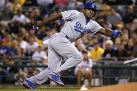 FILE - In this July 23, 2014, file photo, Los Angeles Dodgers' Yasiel Puig leads off first during a baseball game against the Pittsburgh Pirates in Pittsburgh. Twenty-five Cuban-born players appeared in the major leagues this year, a group that includes outfielders Puig and Yoenys Cespedes, and hard-throwing reliever Aroldis Chapman. Fred Claire can see the day when Major League Baseball teams open academies for prospects in Cuba.