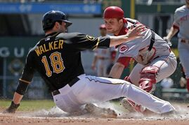 Pittsburgh Pirates' Neil Walker (18) scores ahead of the tag by Cincinnati Reds catcher Devin Mesoraco during the first inning of a baseball game in Pittsburgh Thursday, April 24, 2014. Walker scored from third on a single by Pirates Pedro Alvarez. (AP Photo/Gene J. Puskar)
