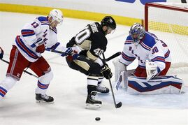 Pittsburgh Penguins' Maxim Lapierre (40) can't get a shot off between New York Rangers goalie Henrik Lundqvist (30) and Kevin Hayes (13) during the first period of a first-round NHL playoff hockey game in Pittsburgh Monday, April 20, 2015.(AP Photo/Gene J. Puskar)