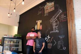 Obby Khan, left, with business partner Johnny Kien, in front of the juicing process wall at their new store Green Carrot Juice Co. Along with business partner Tina Jones (not pictured), the trio will be opening Green Carrot this week.