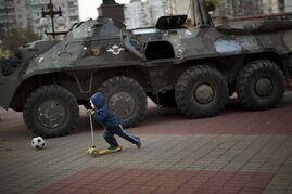 A boy plays next to a Russian armored personnel carrier in central Kiev, Ukraine, Friday, Oct. 24, 2014.