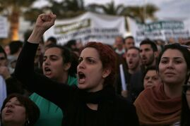 A protestor shouts slogans during an anti austerity demonstration outside a European Central Bank Governing Council meeting at the conference center in capital Nicosia, Cyprus, Wednesday, March 4, 2015. Several thousand demonstrators in Cyprus called for an end to austerity policies they say has driven many in the bailed-out country to poverty. (AP Photo/Petros Karadjias)
