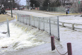 A file photo of water from Sturgeon Creek flowing over Ness Avenue near Valley View Drive in St. James in April, 2009.