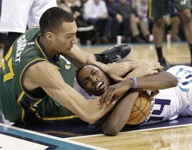 Utah Jazz's Rudy Gobert (27) and Charlotte Hornets' Michael Kidd-Gilchrist (14) battle for a loose ball during the first half of an NBA basketball game in Charlotte, N.C., Saturday, Dec. 20, 2014. (AP Photo/Chuck Burton)