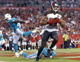 FILE - In this Aug. 16, 2014, file photo, Tampa Bay Buccaneers wide receiver Vincent Jackson (83) eludes Miami Dolphins free safety Louis Delmas (25) and cornerback Brent Grimes (21) to score on a 7-yard touchdown reception from quarterback Josh McCown during the second quarter of an NFL preseason football game in Tampa, Fla. Somehow, despite the turmoil in Tampa last season, Vincent Jackson caught 78 passes for 1,224 yards and seven TDs. Now, he has a somewhat-accomplished veteran throwing to him. (AP Photo/Brian Blanco, File)