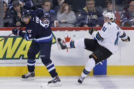 Winnipeg Jets' Evander Kane (9) checks San Jose Sharks' Justin Braun (61) during the first period.