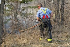 A firefighter swats at flames with a broom.