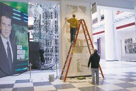 Workers scrape a wall which had a publicity photo of former CBC radio host Jian Ghomeshi in the broadcasting corporation's Toronto offices.
