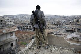 In this picture taken Friday, Jan. 30, 2015, a Syrian Kurdish sniper looks at the rubble in the Syrian city of Ain al-Arab, also known as Kobani. The Islamic State group has acknowledged for the first time that its fighters have been defeated in the Syrian town of Kobani and vowed to attack the town again. (AP Photo)