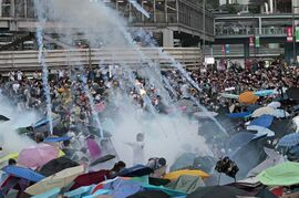 Riot police launch tear gas into the crowd as thousands of protesters surround the government headquarters in Hong Kong Sunday, Sept. 28, 2014. Hong Kong police used tear gas on Sunday and warned of further measures as they tried to clear thousands of pro-democracy protesters gathered outside government headquarters in a challenge to Beijing over its decision to restrict democratic reforms for the city.