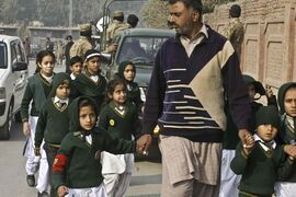 A plainclothes security officer escorts students evacuated from a school as Taliban fighters attack another school nearby in Peshawar, Pakistan, Tuesday. Taliban gunmen stormed a military-run school in the northwestern Pakistani city, killing and wounding scores, officials said, in the worst attack to hit the country in over a year.