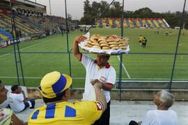 In this Oct. 18, 2014 photo, a vendor sells chipa, a traditional bread with cheese to fans of the Deportivo Capiata soccer team before a national league match against Cerro Porteno in Capiata, Paraguay. Capiata has a tiny fan base, and everything about the club is modest: its dressing room, workout room and stadium amenities. (AP Photo/Jorge Saenz)