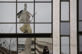 A woman smokes as the 19th century statue of the ancient goddess Athena, is reflected on a building, on Friday, March 27, 2015. Greek bank deposits dropped by more than 7.5 billion euros ($8.2 billion) in February, ramping up pressure on the country's teetering financial system as its government scrambles to reach a deal with creditors within days. (AP Photo/Petros Giannakouris)