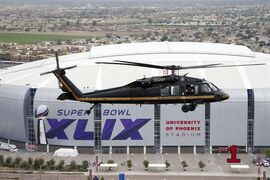 A U.S. Customs and Border Protection Black Hawk helicopter flies above University of Phoenix Stadium, site of Super Bowl XLIX football game, during a security demonstration for the media Monday, Jan. 26, 2015, in Glendale, Ariz. The helicopters and truck-sized X-ray machines that are typically deployed along the U.S.-Mexico border have been brought to the Super Bowl venue to assist with the security effort. (AP Photo/Ross D. Franklin)