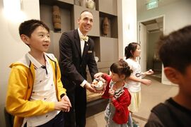 In this July 18, 2014, photo, a South Coast Plaza Shopping Center VIP access lounge butler welcomes Chinese visitors in Costa Mesa, Calif. Chinese tourism is surging and the mall is a popular destination that is doing what it can to keep the buses coming, from accepting China's UnionPay card to providing Mandarin-speaking salespeople. Tourism from China to the United States has soared since the countries signed an agreement in 2007 promoting travel. (AP Photo/Damian Dovarganes)