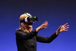 FILE - In this Wed., Sept. 3, 2014 file photo, British television presenter Rachel Riley shows a virtual-reality headset called Gear VR during an unpacked event of Samsung ahead of the consumer electronic fair IFA in Berlin. Oculus, the virtual reality company acquired by Facebook earlier this year for $2 billion, is holding its first-ever developers conference and is expected to discuss the much-anticipated release of its VR headset for consumers. The two-day Oculus Connect conference begins Friday, Sept. 19, 2014. (AP Photo/Markus Schreiber, file)