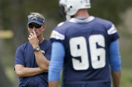 San Diego Chargers head coach Mike McCoy looks on as outside linebacker Jarret Johnson runs a drill at NFL football training camp on Friday, July 25, 2014, in San Diego. (AP Photo)