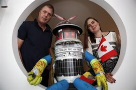 Hitchbot poses with its co-creators Frauke Zeller, an assistant professor at Ryerson University, and David Smith, a professor in the department of communication studies at McMaster University before the start of a welcome reception for Hitchbot at Open Space in Victoria, B.C., Thursday August 21, 2014. THE CANADIAN PRESS/Chad Hipolito