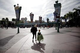 Visitors arrive at the main entrance to the Disney theme parks, Thursday, Jan. 22, 2015, in Anaheim, Calif. Seventy people have been infected in a measles outbreak that led California public health officials to urge those who haven't been vaccinated against the disease, including children too young to be immunized, should avoid Disney parks where the spread originated. (AP Photo/Jae C. Hong)