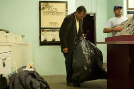 In this Aug. 13, 2014 photo, a man carries a trash bag full of his clothes after getting his laundry done during a Laundry Love event in Huntington Beach, Calif. The organization partners with local laundromats and helps those who are homeless or struggling financially by doing their laundry for free. (AP Photo/Jae C. Hong)