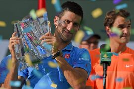 Novak Djokovic, of Serbia, left, poses with the trophy in front of Roger Federer, of Switzerland, right, after the final match at the BNP Paribas Open tennis tournament, Sunday, March 22, 2015, in Indian Wells, Calif. Djokovic won, 6-3, 6-7, 6-2. (AP Photo/Mark J. Terrill)