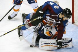 Colorado Avalanche left wing Gabriel Landeskog, front, of Sweden, runs into New York Islanders goalie Chad Johnson in the second period of an NHL hockey game in Denver on Thursday, Oct. 30, 2014. Landeskog was called for goalkeeper interference on the play. (AP Photo/David Zalubowski)