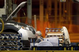 A line worker works on a car at the Ford Motor plant in Oakville, Ont., on Friday January 4, 2013. Ford Motor Co. of Canada says it is adding 1,000 jobs at its plant in Oakville to build the 2015 Ford Edge crossover SUV. THE CANADIAN PRESS/Chris Young