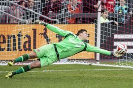 Toronto FC goalkeeper Joe Bendik tips away a shot during second half MLS soccer action against New York Red Bulls in Toronto on Saturday May 17, 2014. Toronto FC coach Greg Vanney will be without goalie Bendik and defenders Steven Caldwell and Mark Bloom for Wednesday's Amway Canadian Championship semifinal first leg in MontrealTHE CANADIAN PRESS/Chris Young